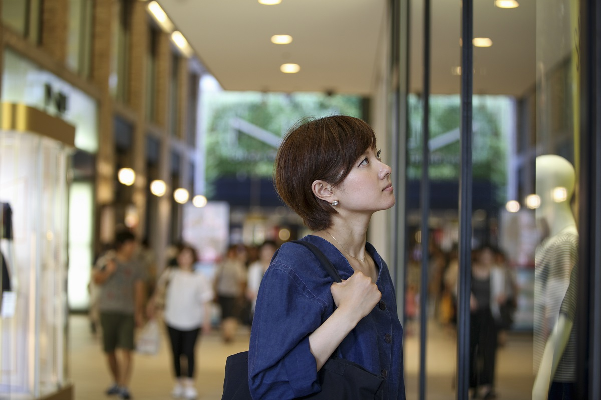 A woman in a shopping mall looking at a shop window display.