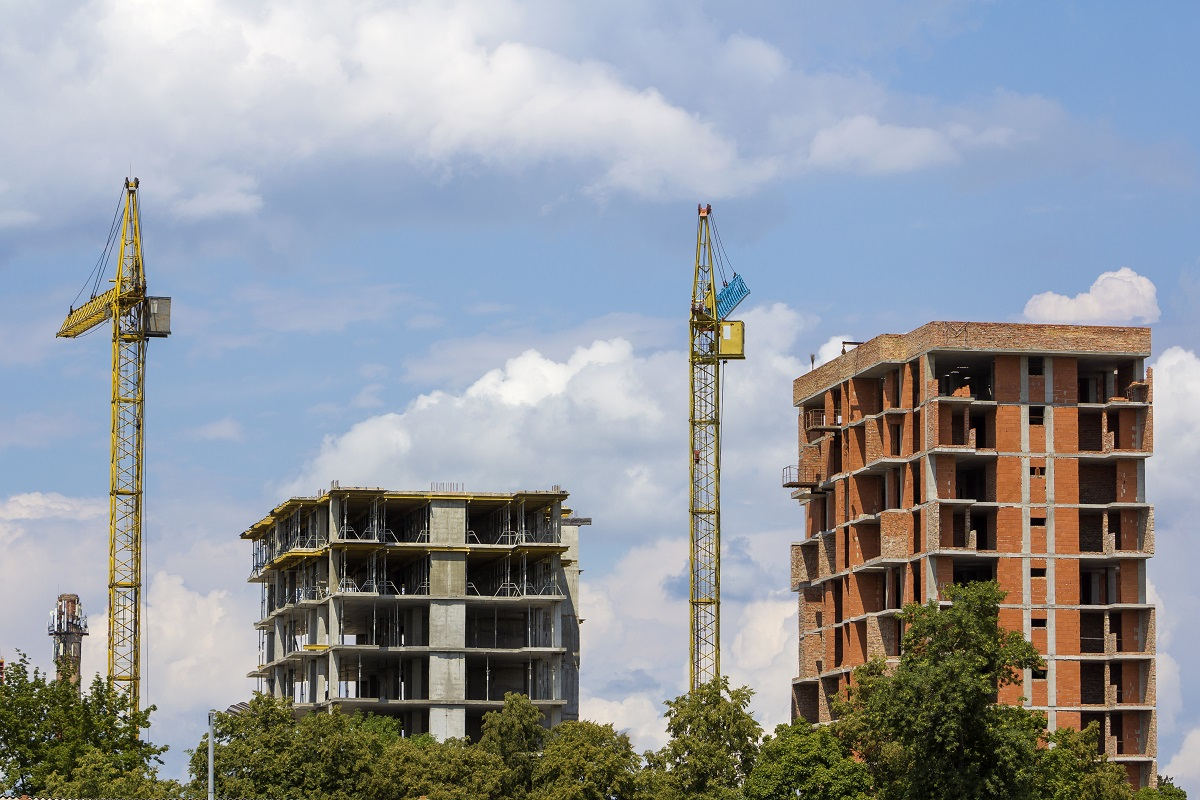 Apartment buildings under construction. Tower cranes on blue sky copy space background.