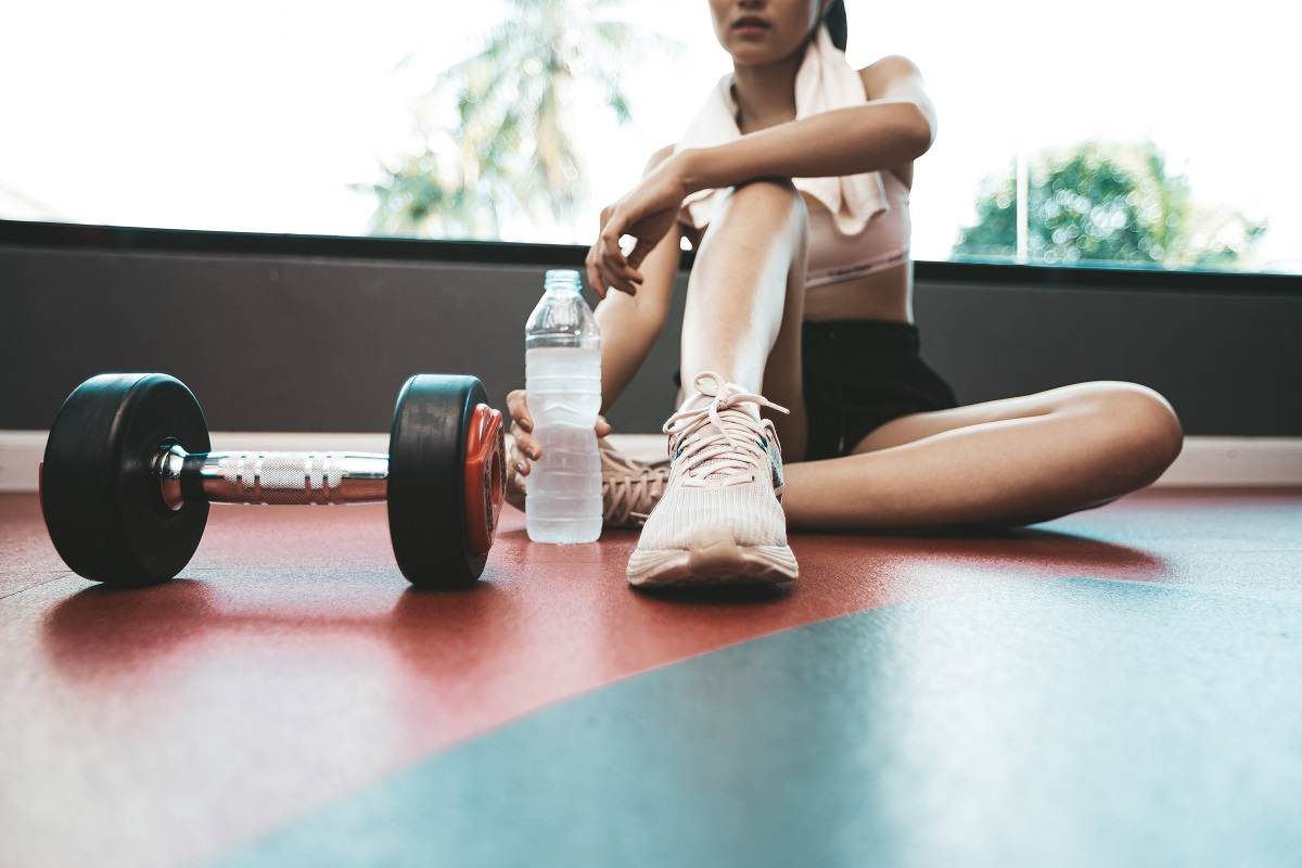 Women sit back and relax after exercise. There is a water bottle