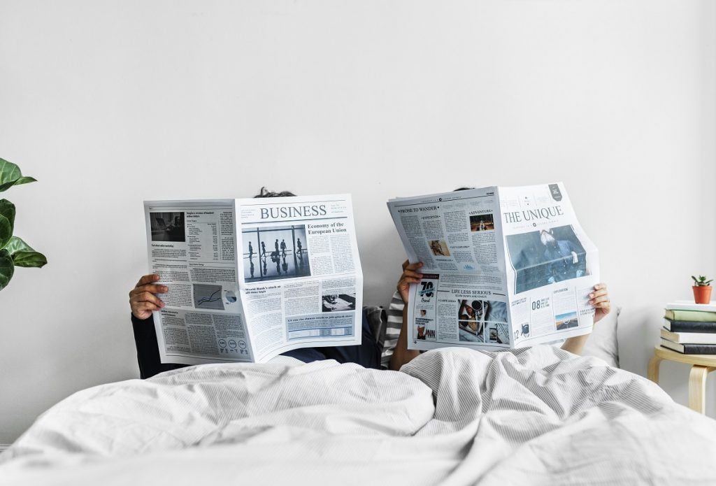 Asian couple reading newspapers in bed